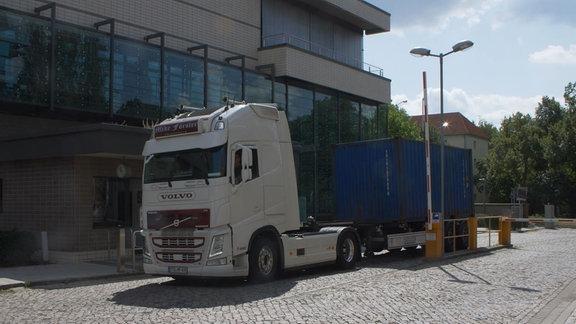 Ein blauer Schiffscontainer steht auf der Ladefläche eines Lkw.