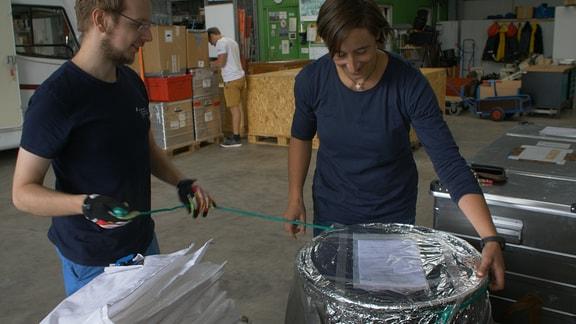 Ein jüngerer Mann im blauen T-Shirt und eine Frau in einem blauen Longsleeve entfernen die silberfarbene Verpackung rund um eine Tonne.