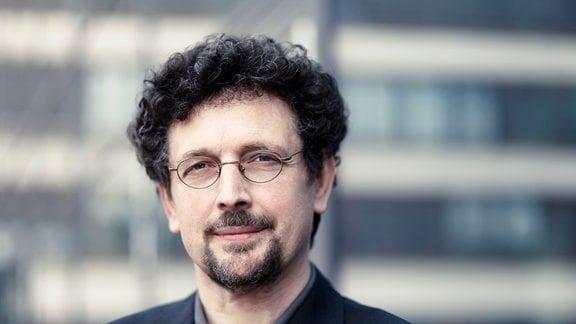 Oberkörper eines Mannes mit lockigen braunen Haaren und Brille.