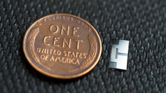 Eine us-amerikanische Ein-Cent-Münze neben einem Ultraschall-Emissionsgerät