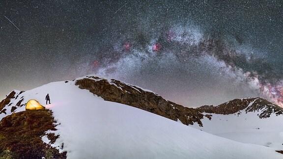 Nachthimmel mit Sternen vor verschneitem Berg, links ein Mensch und ein Zelt