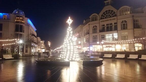 Ein beleuchteter Weihnachtsbaum steht auf einem Platz