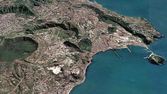 Küstenlandschaft mit Kratern, Wäldern und einer Stadt aus der Vogelperspektive