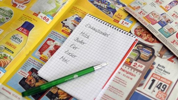 Ein Einkaufszettel liegt auf Prospekten der Lebensmittel-Dicounter