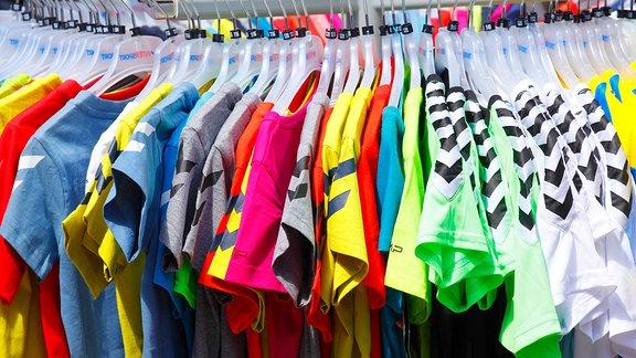 Bunte T-Shirts auf Kleiderbügeln hängend.