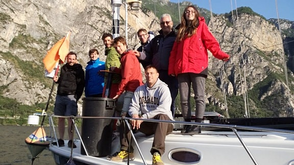 Menschen auf einem Boot auf einem See vor Felskulisse