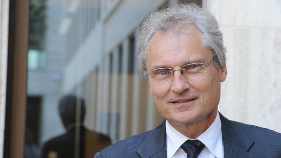 Ein Mann älteren Semesters mit grauen Haaren blickt in die Kamera. Es ist Henning Kagermann, der Leiter der Nationalen Plattform Mobilität