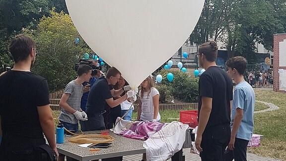 Eine Schülergruppe arbeitet an einem großen Ballon.