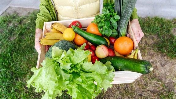 Eine Frau hält eine Kiste mit verschiedenem Gemüse