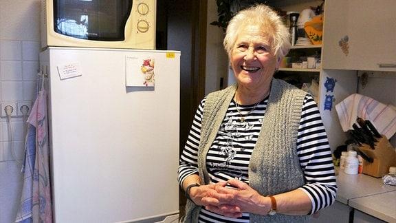 Frau, neben einem Kühlschrank stehend