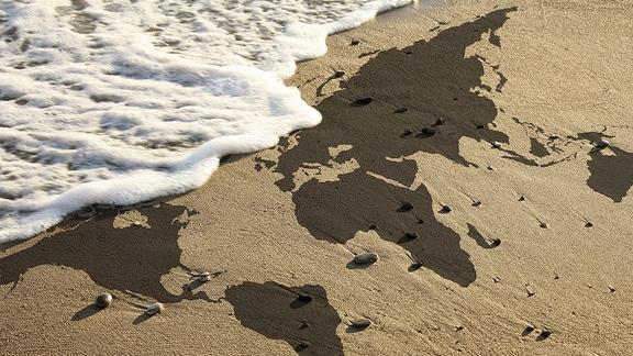 Die Weltkarte im Strandsand und eine Welle bricht am Strand.