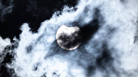 Partielle Sonnenfinsternis vom 10. Juni 2021 über Aachen. Eine leicht bedeckte Sonne. Neben dem Mond sind auch Wolken zu erkennen.