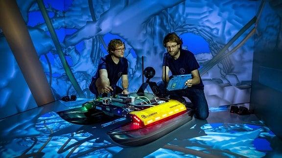 Zwei Männer hocken neben einem Spezialroboter und arbeiten an ihm.