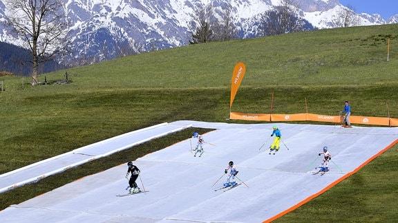 Auf einer grünen Bergwiese liegt eine riesige weiße Bodenmatte. Darauf fahren zahlreiche Skifahrer den Hang runter.