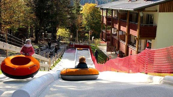 Blick von oeben auf eine Rodelbahn aus Kunstfaser. Ein Kind fährt in einem Reifen den Hang hinunter.