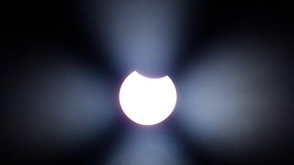 Partielle Sonnenfinternis gegen Mittag, Dabei schiebt sich der Mond zwischen Erde und Sonne.