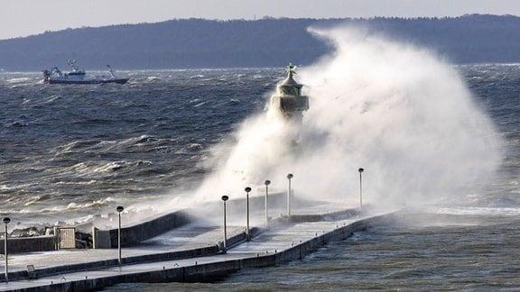 Bei einem Wintersturm  krachen meterhohe Wellen an den Leuchtturm in Sassnitz