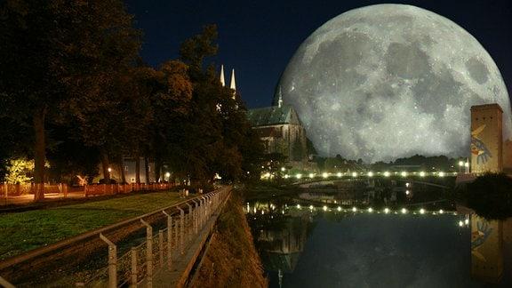 Der Supermond spiegelt sich hinter einem Dom im Fluss.