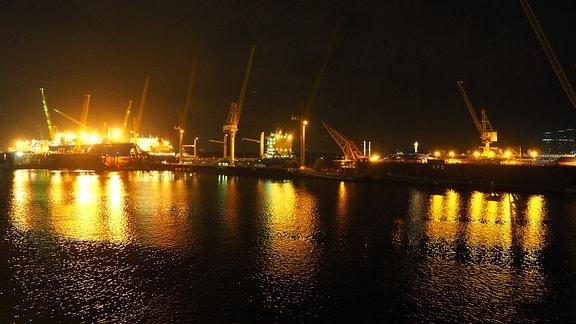 Nachtaufnahme von hell erleuchteten Gebäuden im Hafen von Singapur vom Wasser aus gesehen