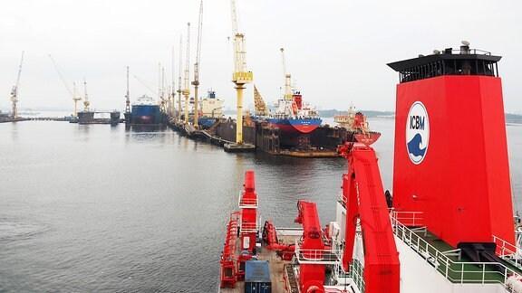Einfahrt des Forschungsschiffs SONNE in den Hafen von Singapur mit Hafenanlagen im Hintergrund