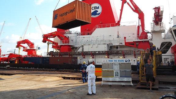 Ein Kran hebt einen orange-farbigen Schiffscontainer vom Forschungsschiff SONNE - mehrere Personen mit Schutzhelmen beobachten diesen Vorgang