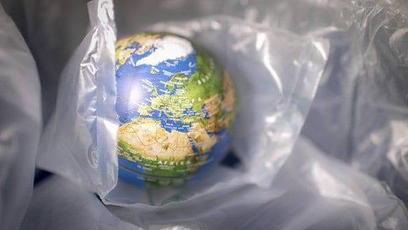 Globus zwischen Plastikverpackungen