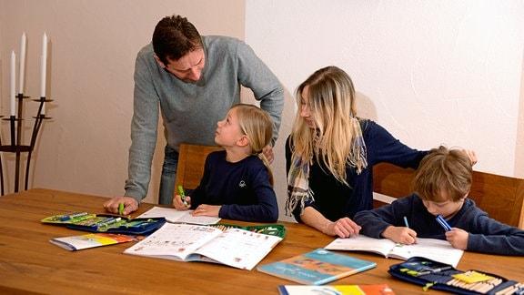 Kinder machen am Küchentisch gemeinsam ihre Hausaufgaben mit den Eltern.