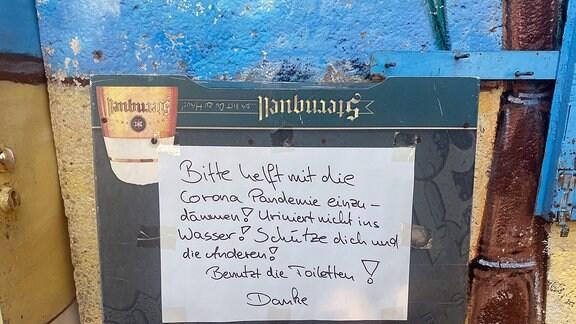 Auf einer Kreidetafel steht die geschriebene Bitte helft die Corona-Pandemie einzudämmen und pinkelt nicht in den See.