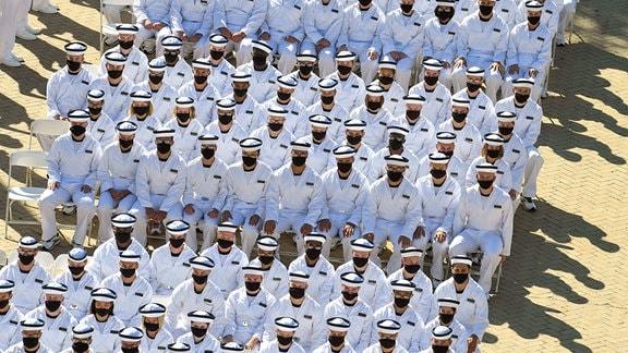 U.S. Navy Zeremonie, bei der die Beteiligten in Uniform Masken tragen