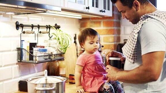 Vater mit kleiner Tochter in der Küche