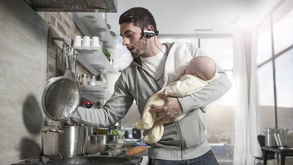 Symbolbild ein Mann hält ein Kind auf dem Arm während er kocht