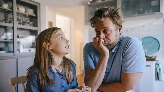Vater und Tochter sitzen an einem Küchentisch. Tochter blickt Vater an, als argumenteire sie, Vater stützt Kinn auf Hand und blickt skeptisch.