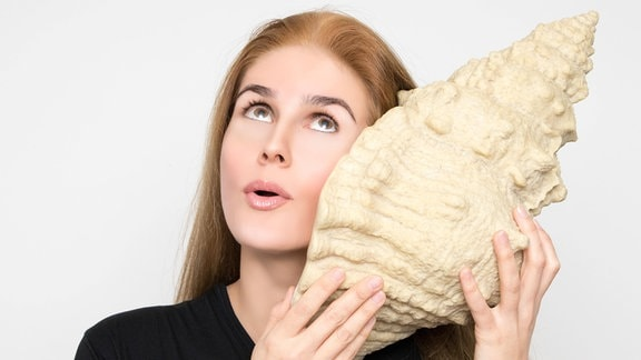 Frau lauscht an großer Venusmuschel