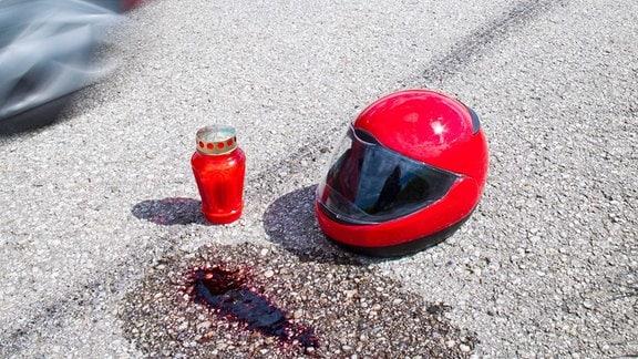 Blutfleck, Kerze und Motorradhelm auf einer Straße