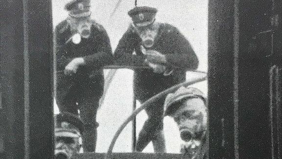 Alte Schwarzweiß- Aufnahme auf der vier Seeleute mit Gasmasken zu sehen sind.