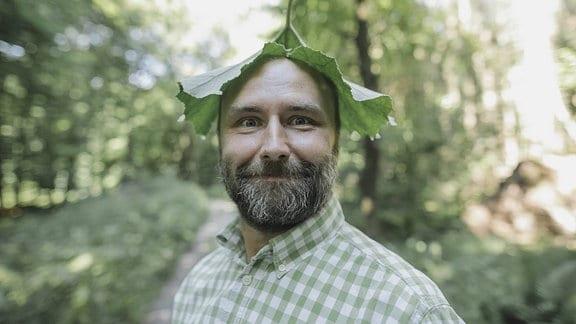Lächelnder Mann mit einem großen Blatt auf dem Kopf