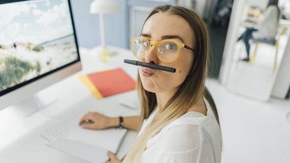 Junge Frau am Schreibtisch mit Stift zwischen Oberlippe und Nase