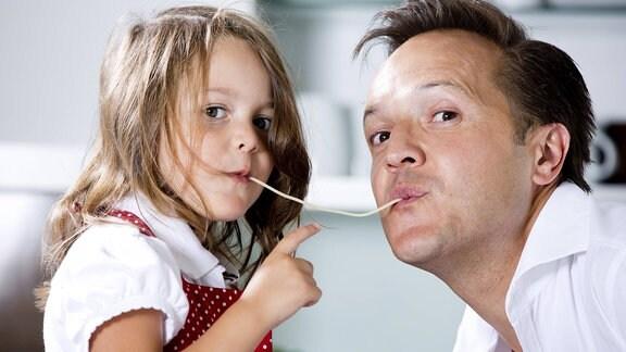 Tochter und Vater essen zusammen an einer Nudel