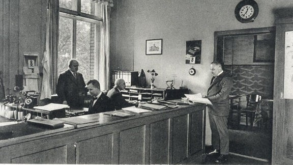 historische Aufnahme / Auf einem Tresen liegen Aktenstapel und Papiere, hinter dem Tresen sitzen zwei Männer in Anzügen und zwei stehen und schauen in Akten.