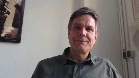 Mann mit schwarz-grauen Haaren und dunklem Pulli vor der Webcam