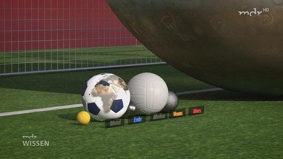 Die Planeten des Sonnensystems sind als Bälle dargestellt und liegen auf der Grundlinie eines Fußballtores. Während die Erde ein Fußball ist, ist der Jupioter eine riesige Kugel, die die Höhe des Tores voll ausfüllt.
