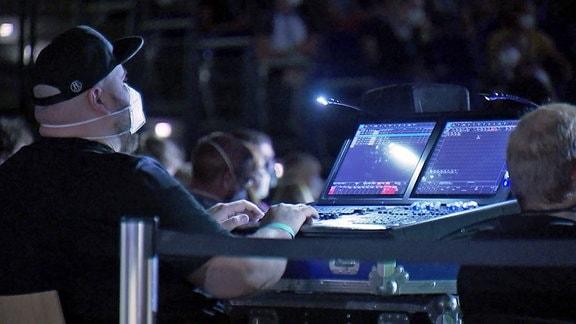 Ein Lichttechniker mit Mund-Nasen-Schutz sitzt während eines Konzertes an seinem Lichtmischpult.