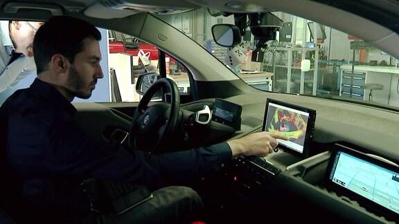 In einem Auto weist ein Mann auf ein Display