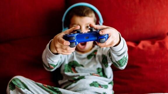 Junge im Schlafanzug trägt während eines Videospiels Kopfhörer