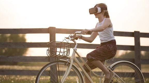 Mädchen oder junge Frau sizt auf einem Fahrrad, fährt entlang eines Zaunes über einen Feldweg und trägt dabei eine Brille für Virtual oder Augmented Reality. Verträumte Stimmung mit warmen Farben.