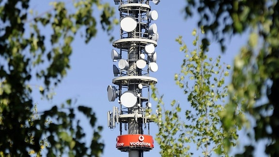 Mobilfunkantennenmast von Vodafone, umrandet von unscharfen Blättern von Bäumen