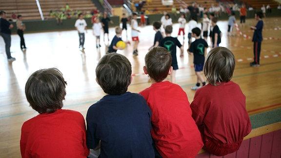 Kinder schauen beim Voelkerballspiel in einer Turnhalle zu