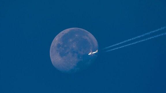 EasyJet Airbus fliegt mit Kondensstreifen vor Vollmond
