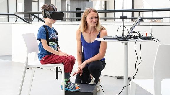 Kind sitzt mit einer Virtual-Reality-Brille auf einem Stuhl, Oberkörper mit Kabeln mit Laptop verbunden, Frau mit blonden, langen Haaren hockt daneben und blickt auf Laptop.