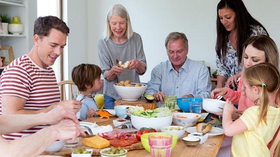 Große Familie sitzt um einen runden Tisch